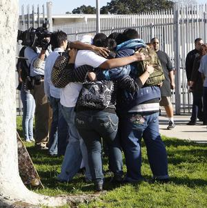 Gardena High School students hug in a circle as they leave the school in California (AP)