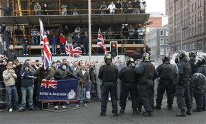 Police Service of Northern Ireland officers in riot gear keep rival supporters apart as The British Army's Royal Irish Regiment parades through Belfast City under tight security in Belfast, Northern Ireland, Sunday, Nov. 2, 2008.  Riot police kept apart rival loyalist and Republican supporters at a parade to honor Northern Ireland members of British armed forces that have recently returned from war zones in Iraq and Afghanistan.  (AP Photo/Peter Morrison)