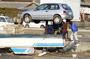 Residents of the seaside town of Yotsukura, northern Japan, inspect under their car as they clear debris from their homes Monday, March 14, 2011, three days after a giant quake and tsunami struck the country's northeastern coast. (AP Photo/Mark Baker)