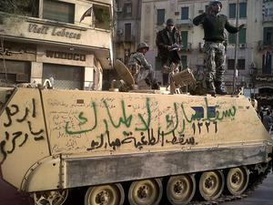 An Egyptian tank enters Tahrir Square in Cairo with anti-Mubarak slogans painted in Arabic
