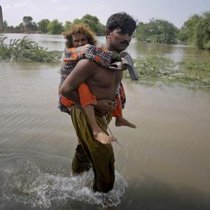 A Pakistani villager carries his mother out of heavy flooding in Pakistan