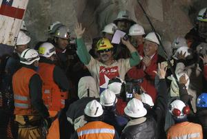 Rescued miner Juan Andres Illanes Palma, center,  third miner to be rescued, salutes at his arrival to the surface from the collapsed San Jose gold and copper mine where he was trapped with 32 other miners for over two months near Copiapo, Chile, Wednesday Oct. 13, 2010.at the San Jose Mine near Copiapo, Chile Wednesday, Oct. 13, 2010. Center right is Chile's President Sebastian Pinera.(AP Photo/Roberto Candia)