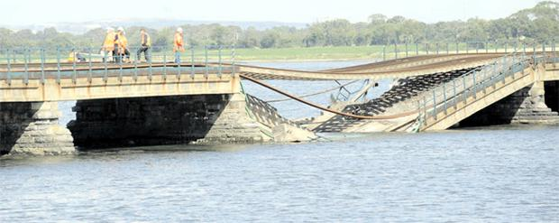 Engineers attend the collapsed railway viaduct across the Malahide estuary. Driver Keith Farrelly used his emergency training to coast his train to safety over the embankment