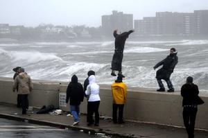 WINTHROP, MA - OCTOBER 29:  People brave high winds and waves along Winthrop Shore Drive as Hurricane Sandy comes up the coast on October 29, 2012 in Winthrop, Massachusetts. Hurricane Sandy, which threatens 50 million people in the eastern third of the U.S., is expected to bring days of rain, high winds and possibly heavy snow to a wide area on the U.S. East Coast. (Photo by Darren McCollester/Getty Images) *** BESTPIX ***