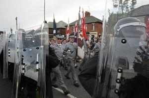 Police accompany the parade past the Ardoyne shops in north Belfast