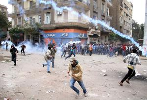 Protesters run from tear gas during clashes with Egyptian riot police in Tahrir Square in Cairo, Egypt, Sunday, Nov. 20, 2011. Firing tear gas and rubber bullets, Egyptian riot police on Sunday clashed for a second day with thousands of rock-throwing protesters demanding that the ruling military quickly announce a date to hand over power to an elected government.  (AP Photo)