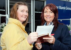 Shirley Anderson, from Ballymena, hands her entry for a prize draw to Anne Hagan on the Ulster Bank stand at Balmoral Show