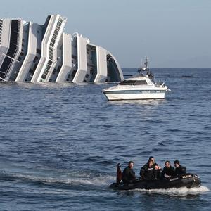 Italian navy scuba divers sail past the cruise ship Costa Concordia (AP)