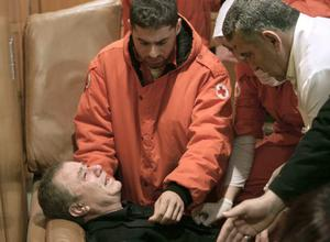 Red Cross workers attend to a grieving man, a relative of passengers of the Ethiopian Airlines plane that crashed into the sea, at Beirut airport, Lebanon, Monday, Jan. 25, 2010.