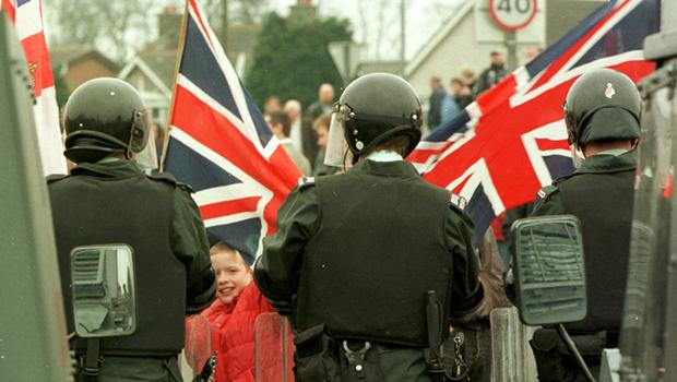 Nationalist Protest March At Garvaghy Road March 1998. A young Loyalist waves the Union Jack at Royal Ulster Constabulary police in riot gear, from the Loyalist side of the town of Portadown, Northern Ireland, as a nationalist-republican protest march,  passed by peacefully down the Nationalist Garvaghy road.