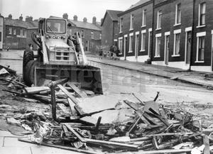 Riots : Belfast. August 1969.  A bulldozer clears away the remains of a barricade consisting of flagstones from the middle of the road at Butler Street, which is at the top end of Hooker Street.  (4/8/69)