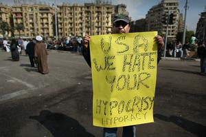 CAIRO, EGYPT - JANUARY 30:  A man in Tahrir Square holds an anti US placard on January 30, 2011 in Cairo, Egypt. As President Mubarak struggles to regain control after five days of protests he has appointed Omar Suleiman as vice-president. The present death toll stands at 100 and up to 2,000 people are thought to have been injured during the clashes which started last Tuesday. Overnight it was reported that thousands of inmates from the Wadi Naturn prison had escaped and that Egyptians were forming vigilante groups in order to protect their homes after Police were nowhere to be seen on the streets. Broadcasts from the Al-Jazeera television network via an Egyptian satellite have now been halted.  (Photo by Peter Macdiarmid/Getty Images)