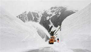 Workers clear snow from the Gotthard across in the Swiss Alps, Monday May 18, 2009, where the highest point is 2,108 meters above sea level. The pass will be reopened on May 27, 2009, after an estimated seven weeks of cleaning works and around 220,000 tons of removed snow, according to the removal team leader.  The pass connects the German-speaking part of Switzerland with the Italian-speaking region of the country.(AP Photo/Keystone,  Urs Flueeler)