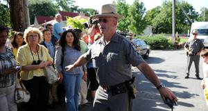 A New York State Trooper clears spectators and journalists from the driveway for a shuttle bus with wedding guests