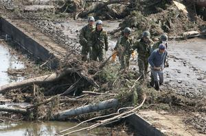 SENDAI, JAPAN - MARCH 14:  Members of the Ground Self-Defense Forces help a man evacuate the area when a warning of tsunami is issued after a 9.0 magnitude strong earthquake struck on March 11 off the coast of north-eastern Japan, on March 14, 2011 in Sendai, Japan. The quake struck offshore at 2:46pm local time, triggering a tsunami wave of up to 10 metres which engulfed large parts of north-eastern Japan. The death toll is currently unknown, with fears that the current hundreds dead may well run into thousands.  (Photo by Kiyoshi Ota/Getty Images)