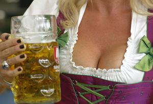 MUNICH, GERMANY - SEPTEMBER 20:  A traditionally Bavarian dressed woman enjoys drinking beer at Schottenhamel beer tent during day 2 of the Oktoberfest beer festival on September 20, 2009 in Munich, Germany. The riflemen's parade marks day 2 of the Munich Oktoberfest beer festival.  (Photo by Johannes Simon/Getty Images)