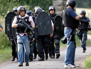 Armed police escort a man along a track near Wagtail Farm in the village of Rothbury as the search for armed fugitive Raoul Moat goes on in the north-east of England on July  7, 2010