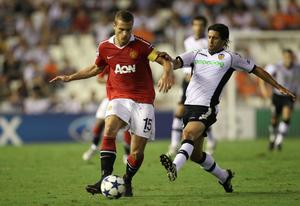 Nemanja Vidic of Manchester United holds off a challenge from Alejandro Dominguez of Valencia during the UEFA Champions League Group C match between Valencia and Manchester United at the Mestalla Stadium on September 29, 2010 in Valencia, Spain