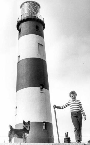 Eleven-year-old Jennifer McBride, of Rugby Avenue, Belfast, with her dog Skip, looks out to sea from St John's Point lighthouse on the Co.Down coast, near Ardglass. 9/8/1982