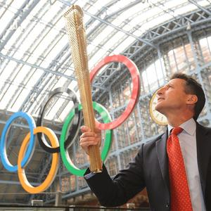 London 2012 chairman Lord Coe holds aloft the golden Olympic Torch
