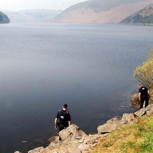 Police at the scene of the accident at Bwlch y Gle Dam, Clywedog (PA)