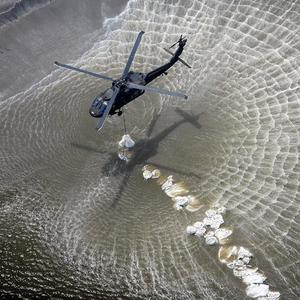 Helicopters drop sandbags to try and stem an oil slick in the Gulf of Mexico