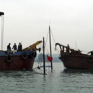 Vietnamese workers try to hoist the sunken vessel out of the water at Ha Long Bay, Vietnam