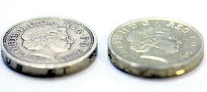 Spot the fake: The real £1 coin, complete with its ring of dots, is the one on the left