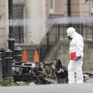 Forensic officers examine the scene where a car bomb exploded outside the Strand Road police station in Londonderry