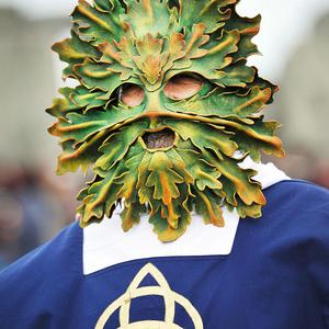 A druid with a green man facemask joined the sunrise celebrations of the Summer Solstice at Stonehenge, Wiltshire