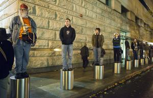 PORTLAND, OR - NOVEMBER 13: People stand cylindrical parking barriers as they observe a crowd at the Occupy Portland camp November 13, 2011 in Portland, Oregon.  In spite of an eviction notice for early Sunday morning, Portland police delayed closing two downtown parks early today as thousands of people converged to support the Occupy Portland movement. (Photo by Natalie Behring/Getty Images)