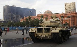 Egyptian armored vehicles take position outside the Egyptian museum in Cairo Sunday, Jan. 30, 2011. The Arab world's most populous nation appeared to be swiftly moving closer to a point at which it either dissolves into widespread chaos or the military expands its presence and control of the streets. At left is the burned ruling party headquarters. (AP Photo/Tara Todra Whitehill)