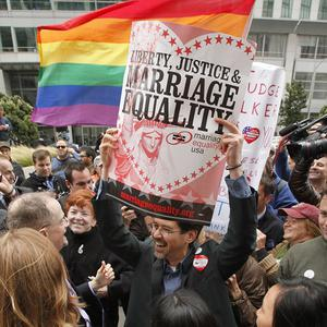 A man holds up a sign while celebrating the decision in the United States District Court proceedings challenging Proposition 8 (AP)