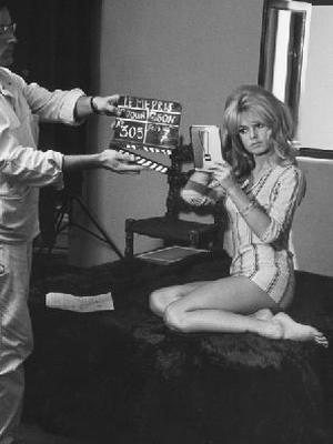 French actor Brigitte Bardot uses a mirror to check her blonde locks on the set of 1963 film 'Contempt'.