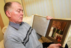 Gerard McErlane looks at pictures of his sons Thomas and John who were murdered in North Belfast.