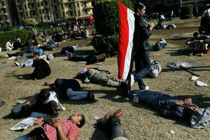 CAIRO, EGYPT - JANUARY 30:  Exhausted Egyptians rest on the grass in in Tahrir Square after days of protests on January 30, 2011 in Cairo, Egypt. As President Mubarak struggles to regain control after five days of protests he has appointed Omar Suleiman as vice-president. The present death toll stands at 100 and up to 2,000 people are thought to have been injured during the clashes which started last Tuesday. Overnight it was reported that thousands of inmates from the Wadi Naturn prison had escaped and that Egyptians were forming vigilante groups in order to protect their homes after Police were nowhere to be seen on the streets.  (Photo by Chris Hondros/Getty Images)