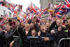 Crowds wave Union flags in Enniskillen, County Fermanagh, as they wait for the arrival of Queen Elizabeth II during a two-day as part of the Diamond Jubilee tour. PRESS ASSOCIATION Photo. Picture date: Tuesday June 26, 2012. See PA story ROYAL Queen. Photo credit should read: Niall Carson/PA Wire