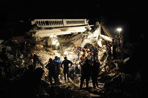 This photo provided by the U.S. Navy shows members of the Los Angeles County Fire Department Search and Rescue Team clearing debris at a collapsed building in downtown Port-au-Prince, Jan. 17, 2010. (AP Photo/U.S. Navy, Justin Stumberg)