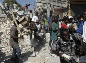 People fight for goods taken from collapsed stores in Port-au-Prince, Monday, Jan. 18, 2010. Violence and looting broke up in Port-au-Prince as earthquake survivors scavenged for anything they could find in the ruins. (AP Photo/Francois Mori)