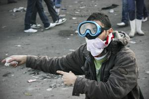 An Egyptian protester gestures during the clashes with Egyptian riot police, unseen, in Cairo, Egypt, Monday, Nov. 21, 2011. Police are clashing for a third day in Cairo's central Tahrir Square with stone-throwing protesters demanding the country's military rulers quickly transfer power to a civilian government. (AP Photo/Mohammed Abu Zaid)