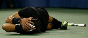 Rafael Nadal of Spain rolls on the ground in celebration of his win over Novak Djokovic of Serbia during their men's singles final on day fifteen of the 2010 U.S. Open