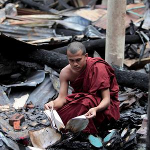 A Bangladeshi Buddhist monk checks the remains of burned religious books at a temple which was torched in an overnight attack in Ramu (AP)
