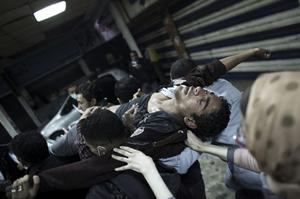 Protesters evacuate a wounded man during clashes with Egyptian riot police to a field hospital near Tahrir Square in Cairo, Egypt, Monday, Nov. 21, 2011. Security forces fired tear gas and clashed Monday with several thousand protesters in Cairo's Tahrir Square in the third straight day of violence that has killed at least two dozen people and has turned into the most sustained challenge yet to the rule of Egypt's military. (AP Photo/Tara Todras-Whitehill)