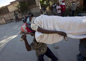 People carry an injured earthquake survivor in Port-au-Prince, Haiti, Thursday, Jan. 14, 2010.
