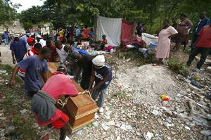 People carry a coffin containing the remains of an earthquake victim to a home for burial in Port-au-Prince, Haiti, Tuesday, Jan. 14, 2010