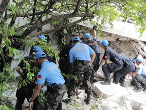 In this Wednesday, Jan. 13, 2010 photo released by the Philippine Mission to the United Nations, police officers from the Philippines and China search for colleagues who may be trapped in the rubble of the United Nations Police Headquarters in Port-au-Prince