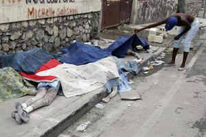 A woman lifts a cloth to see the face of an earthquake victim lying in the street in Port-au-Prince, Haiti, Thursday, Jan. 14, 2010