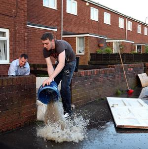 Residents empty buckets of water from their homes in Hebburn (AP)