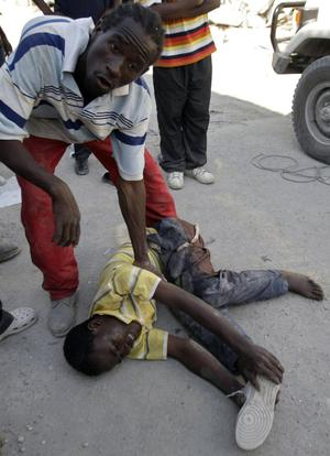 A man lies on the floor as he grimaces in pain after being injured during scuffles among people taking goods from quake-damaged stores in downtown Port-au-Prince, Haiti, Monday, Jan. 18, 2010. Violence and looting broke up in Port-au-Prince as earthquake survivors scavenged for anything they could find in the ruins. (AP Photo/Francois Mori)