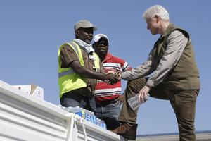Former president and U.N. special envoy for Haiti Bill Clinton, right, talks to airport workers unloading relief supplies at the airport in Port-au-Prince, Monday, Jan. 18, 2010.